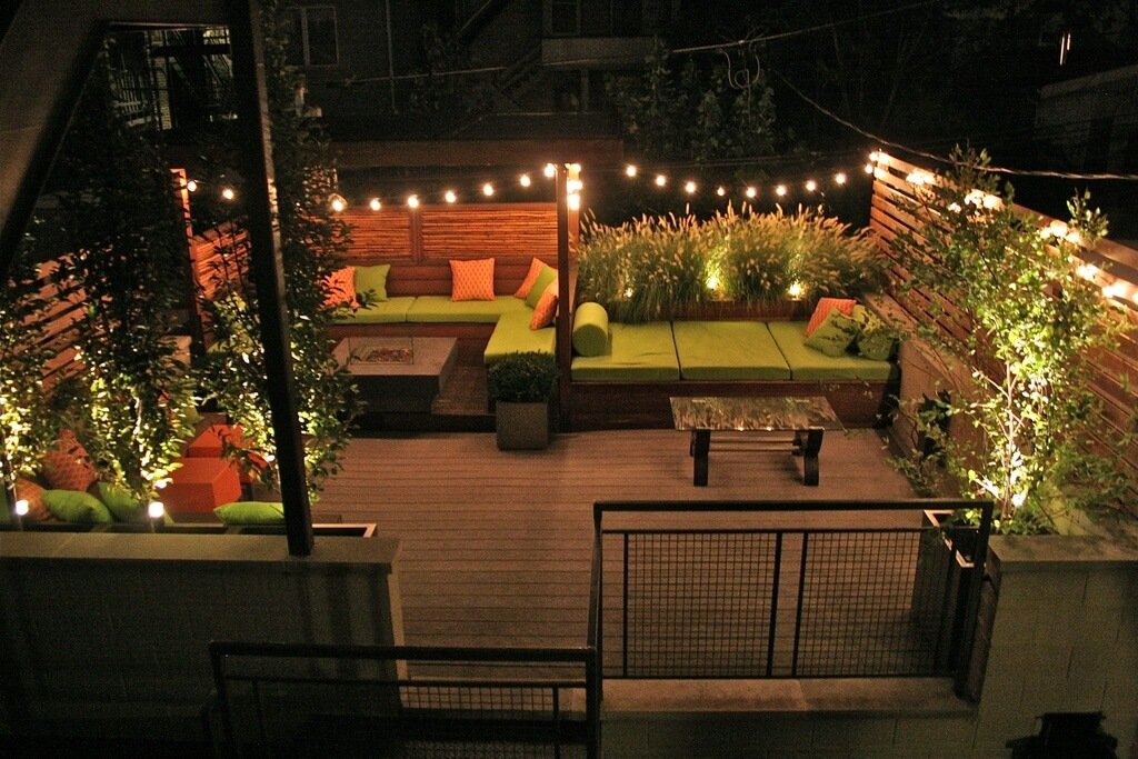 A garden rooftop patio all lit up at night by string lights. The patio is enclosed by wooden fences and tall foliage.