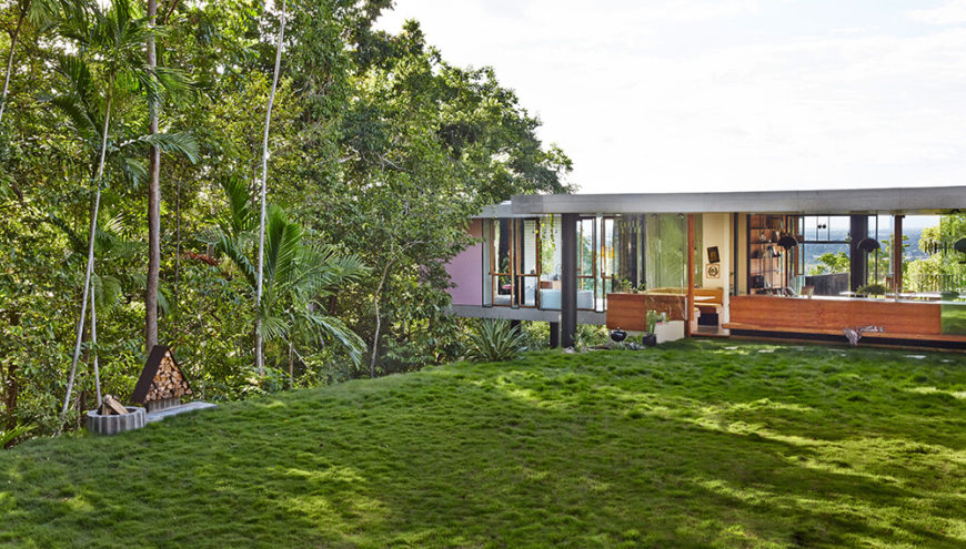 Across the top level we see a sprawling lawn, and through the house we see the rainforest beyond.
