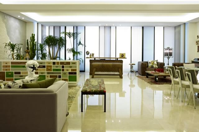 A small forest stands sentinel in the corner of the room and highlights the subtle uses of green in the accents throughout the space. Shades of brown are used to balance the use of white in the rest of the room.