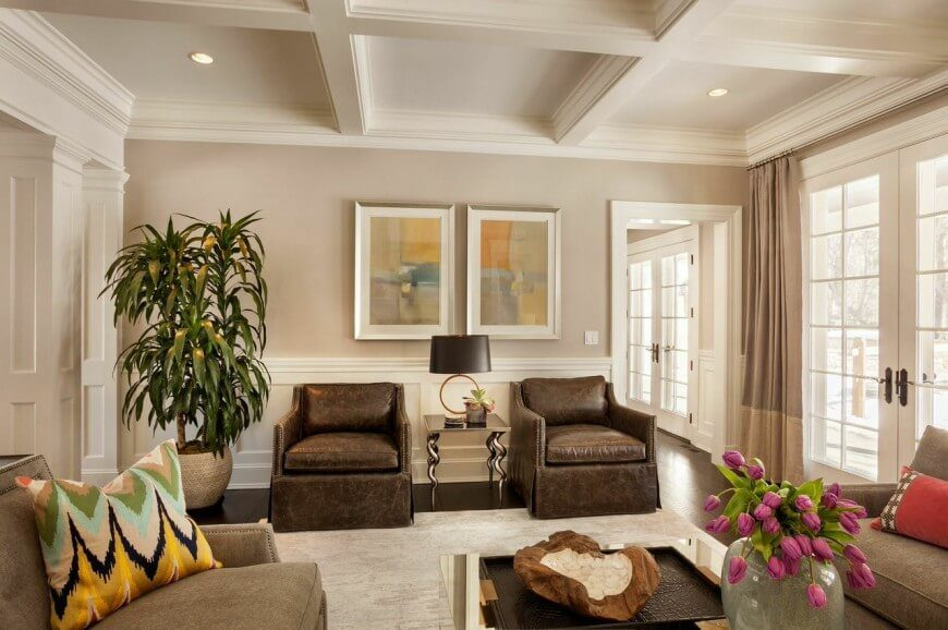 Placing the tree in the corner of this room balances the height and adds a pop of color that accents the subtle use of green in the room. Starting with a neutral base, splashes of color can be found throughout the room.