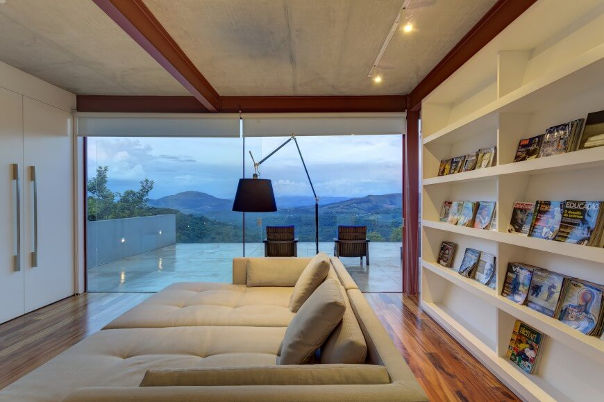 Spacious home library featuring a massive sofa bed set on the hardwood flooring. There's a large bookshelf on the back of the sofa. The room also features a glass door leading to the home's private outdoor lounging space.