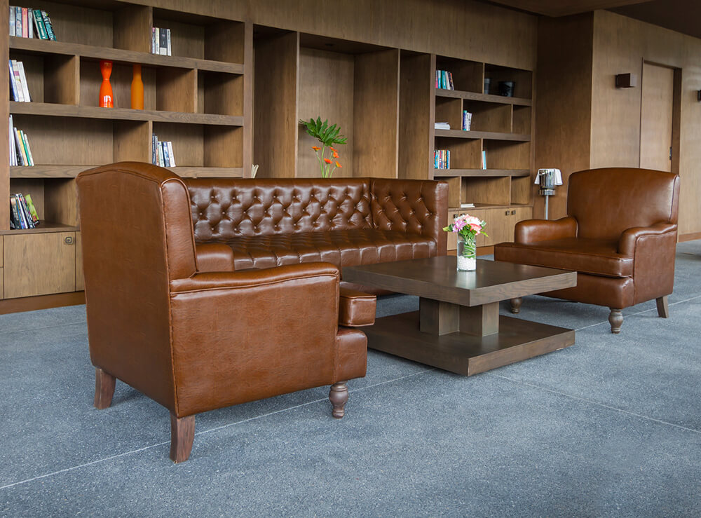 A home library featuring large tiles flooring and brown leather seats with a stylish center table.
