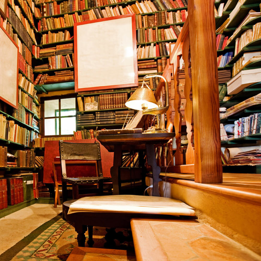 A close up look at this home library's study desk. The multiple bookshelves look so amazing.