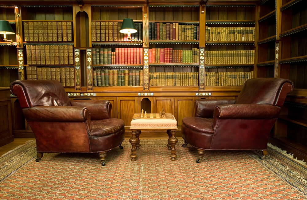 This home library with large bookshelves features a classy rug and brown leather seats with a chess board set as a centerpiece.