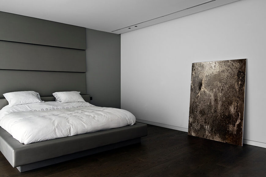 The primary bedroom returns to the more somber palette of the public areas of the home, with a singular painting resting against the plain white wall. A massive ceiling height headboard frames the large grey bed.