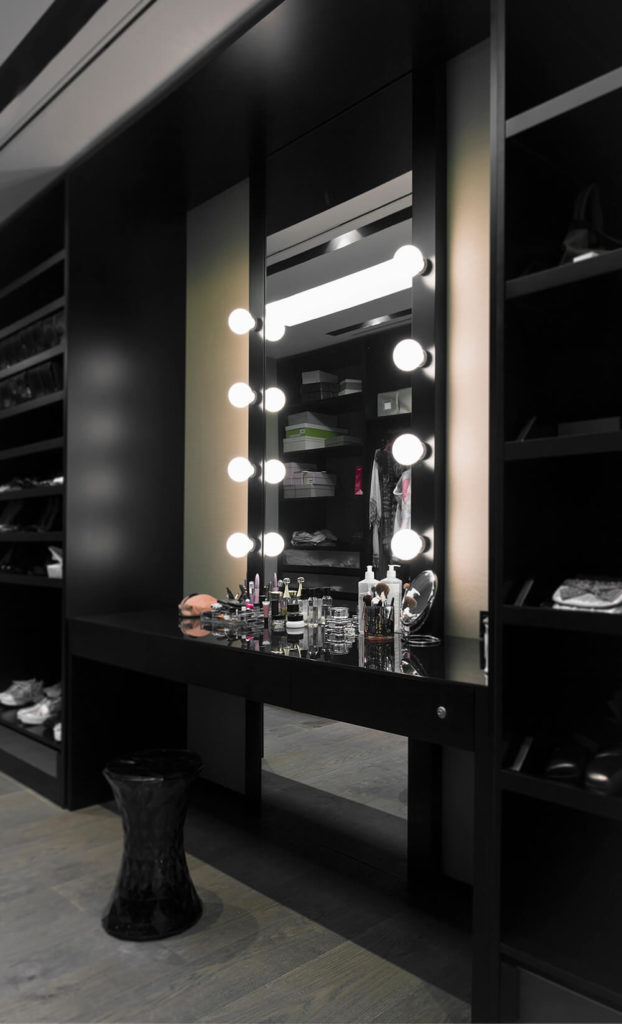 The massive walk-in closet features this dark and elegant makeup desk, sandwiched between black full height shelving. The muted hardwood flooring here acts in subtle contrast.