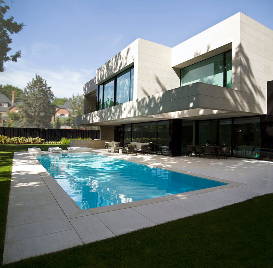 The ground floor opens via large glass panels onto the sleek and minimalist patio and pool area. The structure-wide swath of continuous glass makes for a blurred line between indoor and outdoor settings.