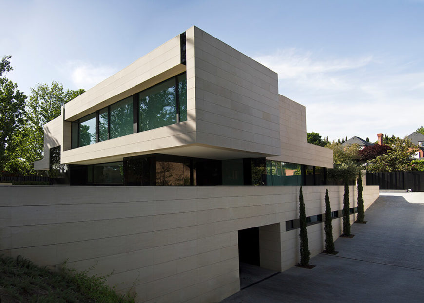 Moving around to the side of the home, we can see how the driveway gently slopes to the basement level, where there is secluded parking. The minimalist concrete space is lined with manicured trees for a touch of natural beauty.