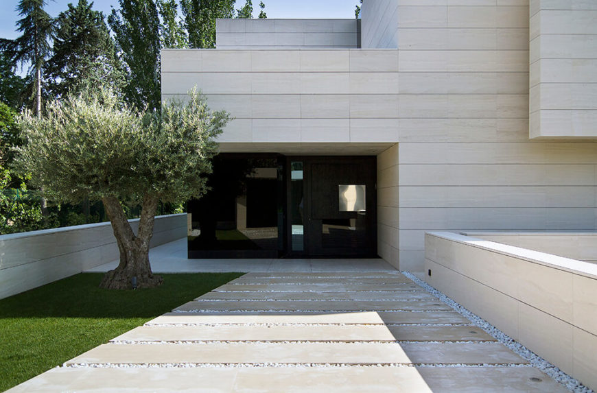 The main entryway sets a series of large concrete slabs over a white stone bed, buffered by a slim lawn with a tree to the left. The mixture of shaped and natural materials informs the entire look.