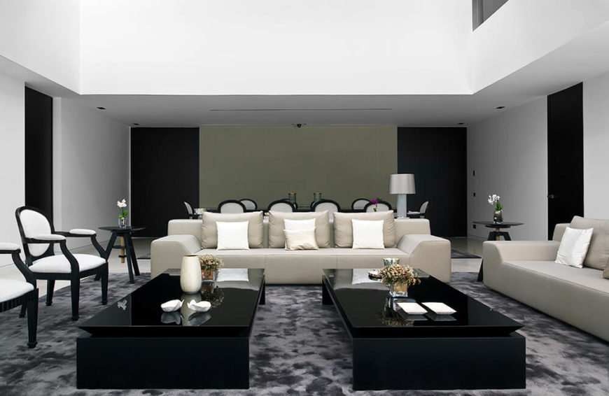 The living room is the perfect place to begin our journey through the home. The large two-story space features the high contrast neutral tones of the exterior, with black glossy tables and light beige furniture in a white room.
