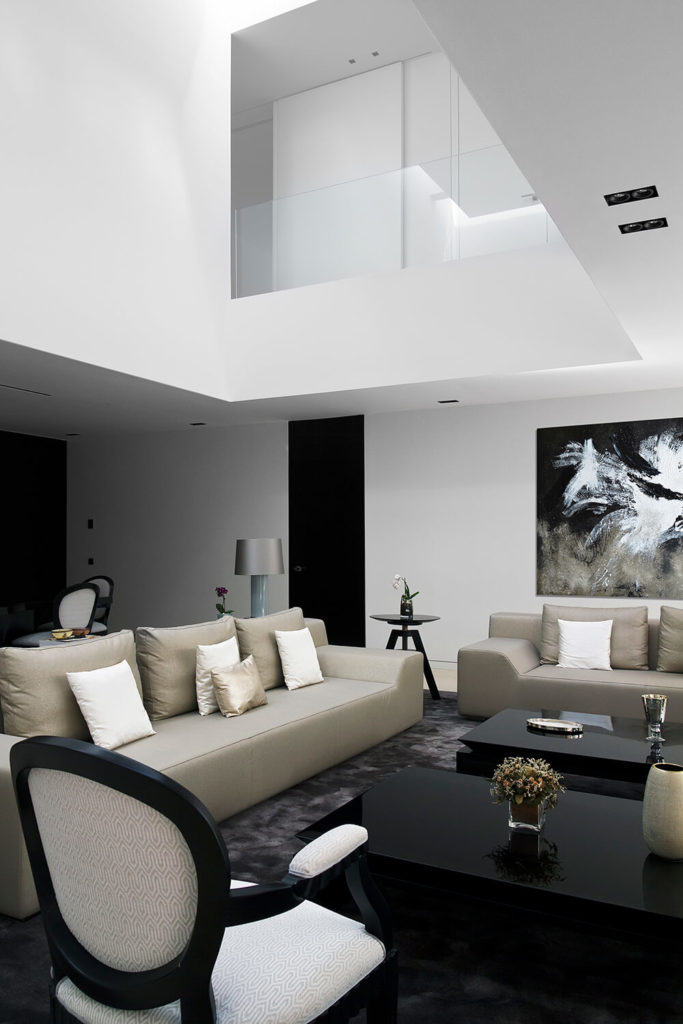 In the upper area of the double height living room, we can see an opening to the second floor, allowing for spectacular views over this open-plan space. The bespoke modern furniture offers rich detail and texture despite the limited palette.