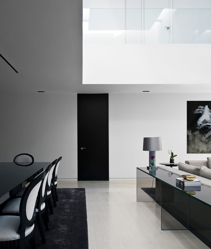 The open design of the home means that the dining room is incorporated into the larger living room space. At right, an all-glass end table rests against the back of the sofa, helping define the area.