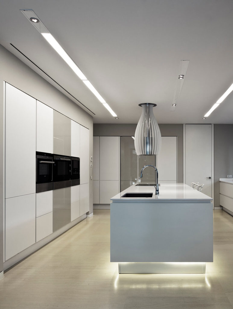 The island features subtle lighting around the bottom, making the beige flooring glow. The oven setup is built into the glossy cabinetry at left.