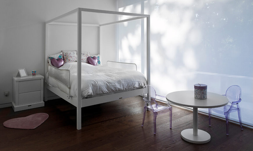 This childrens' bedroom features an all-white look in contrast with the rich hardwood flooring. To the right, a discreet screen provides privacy and shade from the balcony.