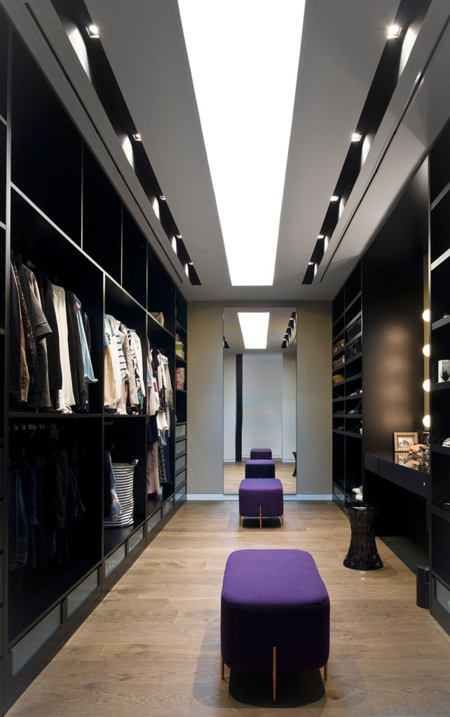 Here in the walk-in closet we see another subtle burst of color, courtesy of a set of bold purple benches.