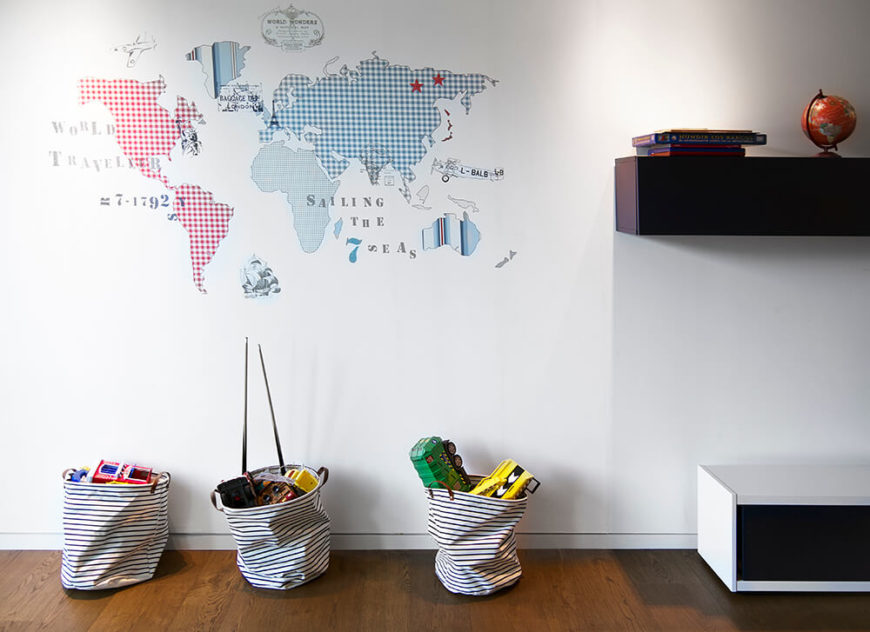 A uniquely textured world map appears on the wall in a muted burst of colors, with other playful items scattered around the room.