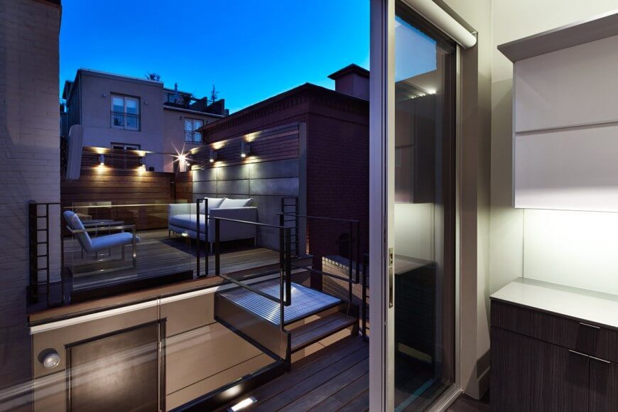 A rooftop patio enclosed by the home with a small catwalk and hallway connecting to the top floor of the building.