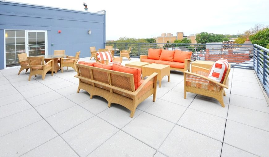 A contemporary spacious rooftop patio with several intimate seating areas and dining areas overlooking the city below.