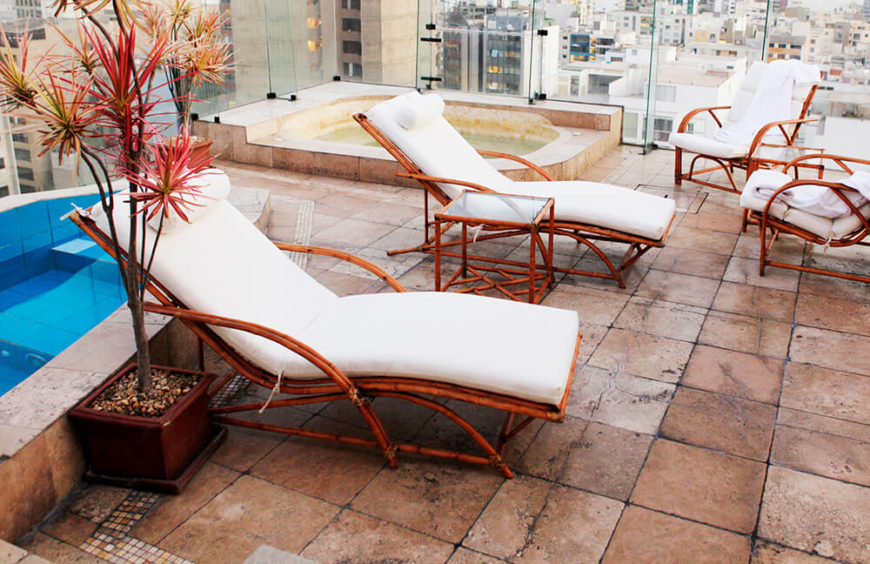 An older rooftop patio complete with a small pool and a jacuzzi. Seating consists of lounge chairs and armchairs made of bamboo.