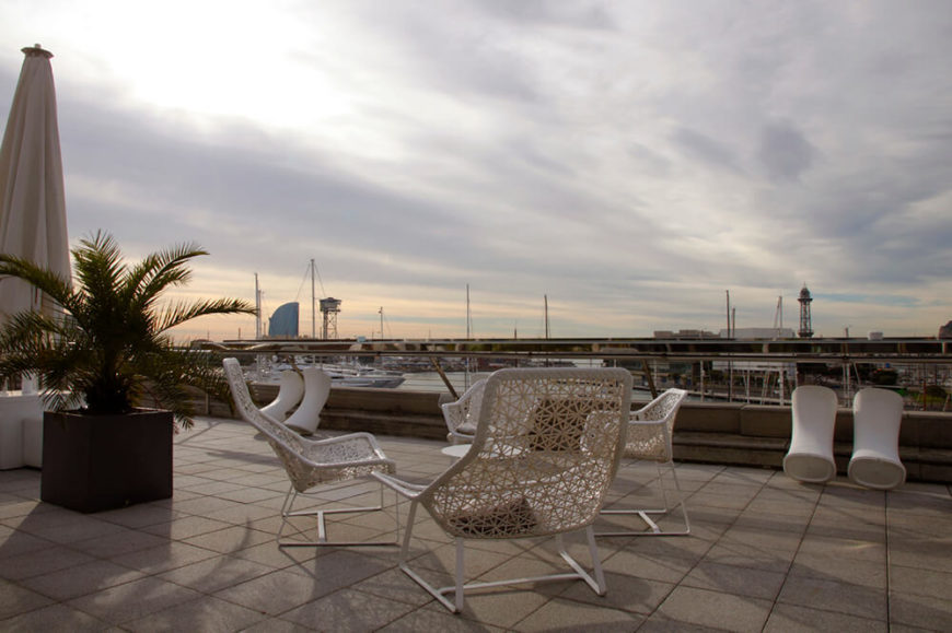 A rooftop patio with white furniture overlooking a large marina. Also visible in the background is a city skyline, including skyscrapers.