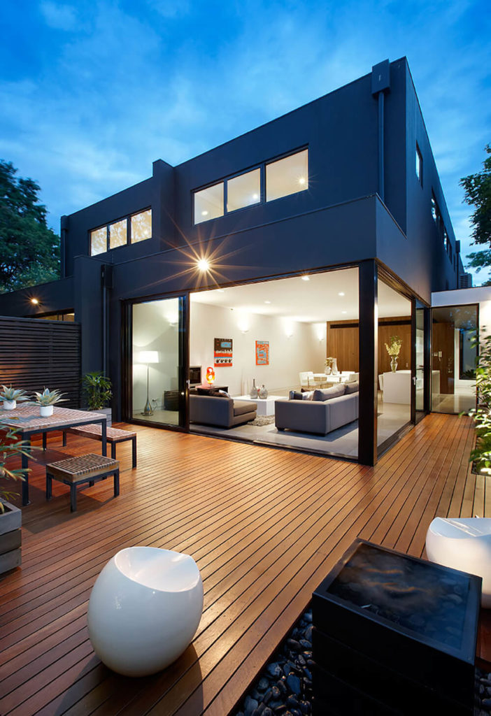 The rear of the home is where the real magic happens, with an open design and large panels of glass that integrate the living room with the surrounding patio. Rich wood cladding is dotted with greenery and interesting water features. The interior space seamlessly integrates with the outdoors here.