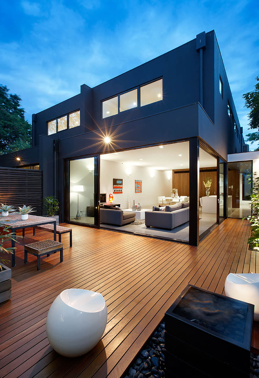 This deck features classy seats and a dining table set along with some plants on the side.