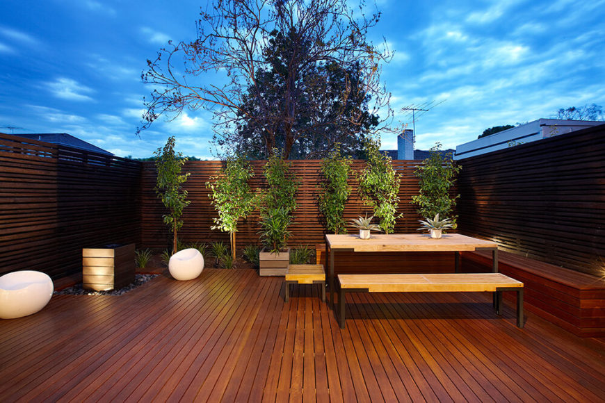 The patio is an exercise in rich minimalism, with sumptuous timber flooring and privacy fending that wraps the entire space, dotted with manicured plant life. Novel white bean chairs and a traditional picnic table make for a truly useful space.