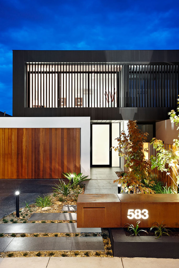 Returning to the front of the home, we can get a close look at the garden features, including a bespoke wood piece with the glowing address etched in. The rectangular steps are settled into a bed of polished stones and strategically lit via a set of subtle black ground lights.