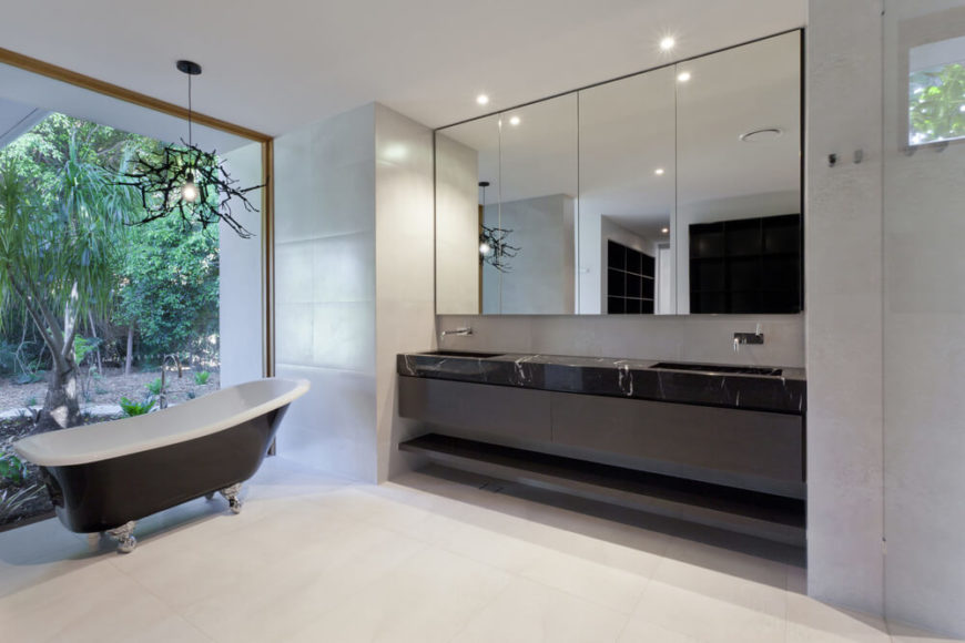 A fine marble counter is home to two sinks, in front of a large mirror in this minimalist bathroom. A clawfoot tub stands to the side, in front of a large window with a view of an outdoor garden.