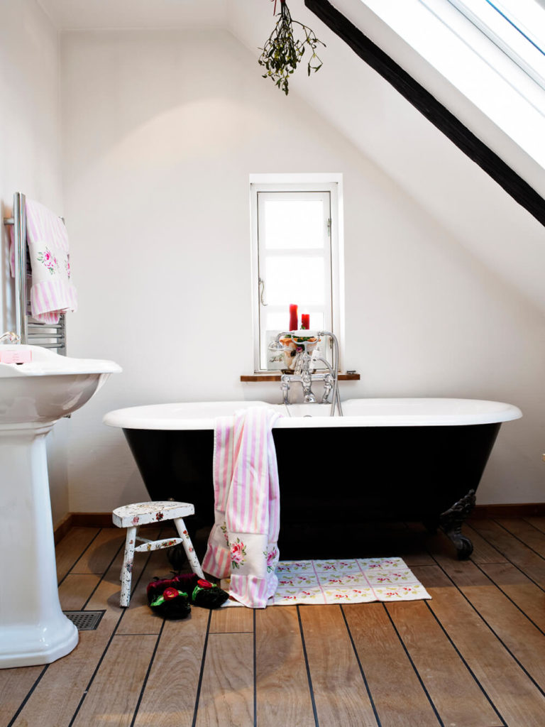 A simple and modest space, this bathroom features a black clawfoot tub sitting atop a defined wood grain floor. A porcelain pedestal sink sits to the side and accompanies the tub in this small bathroom space.