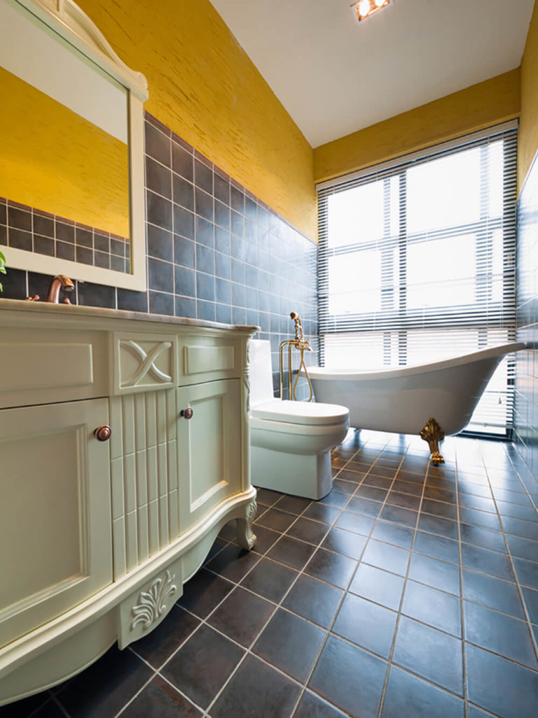 The upper third of this bathroom wall is bright and vibrant, while the floor and the lower section of the walls are covered in a dark brown tile. The contrast makes this space unique. A large clawfoot tub sits close to the floor to ceiling windows, leaving it illuminated by the natural light.