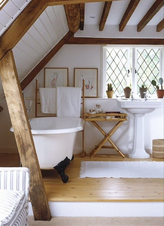 Large wooden rafters line the ceiling and run down the angled walls in this bathroom. One single rafter is braced against the angled ceiling, serving as a support system as well as a small divider for the bathroom space. The combination of natural wood grain and white utilities makes for a clean and relaxing space.