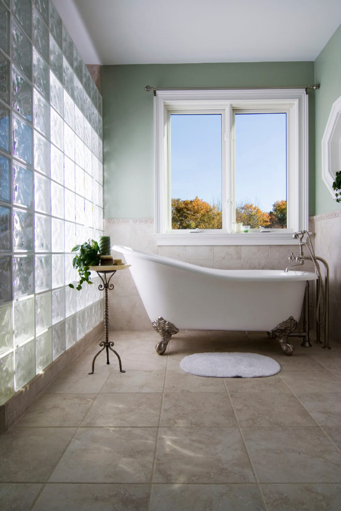 Large square tiles run halfway up the wall in this bathroom and serve as a backsplash for the tub. A glass brick wall is featured in this bathroom and allows for plenty of natural light to spill into the room.