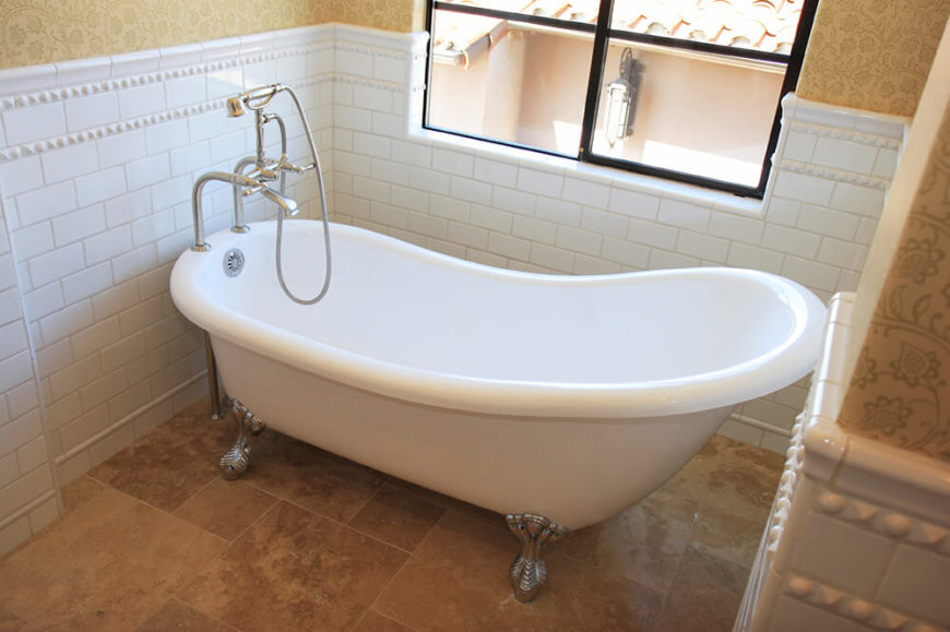 This clawfoot tub sits upon textured tile and directly beneath a window. This space is well lit by natural light, and the white tile running halfway up the wall serves as a backsplash for the tub area.