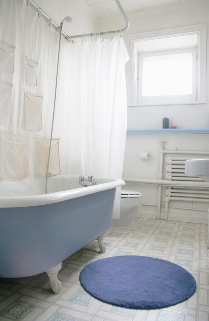 This bright bathroom is illuminated by natural light, however, the stark white walls combined with the light blue accents make help to make this space as bright and airy as possible. The large clawfoot tub contributes to the accents in the room with a blue outer surface.