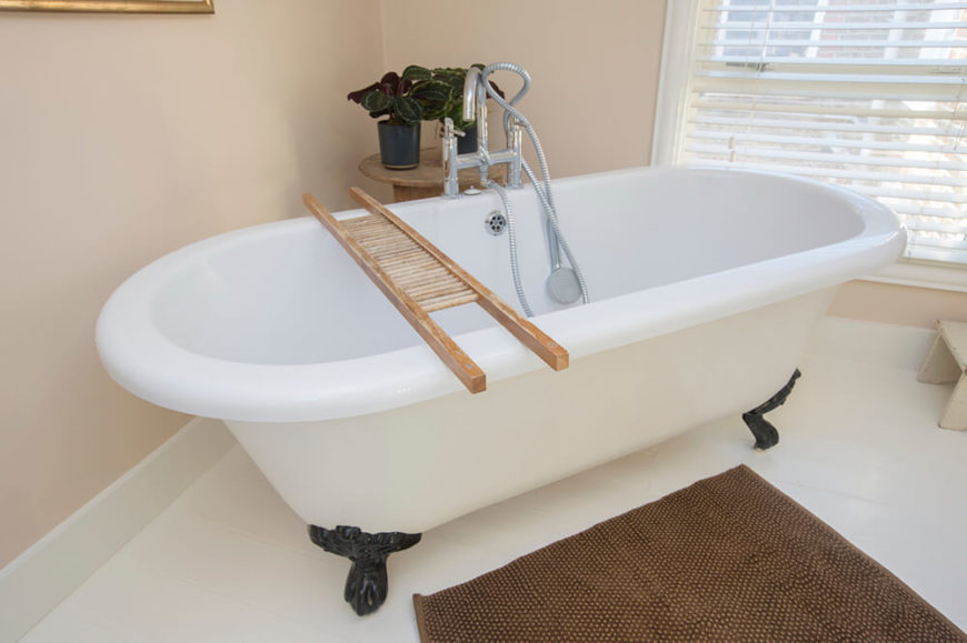 A simple and crisp bathroom, featuring a clawfoot tube upon a white tile floor. Before the tub lies a small rug to soak up spilled water, and behind is a small table holding plants that help to accent the space.