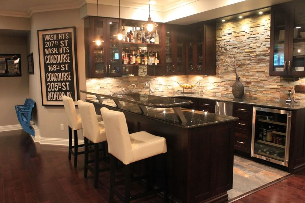 This home features a bar area with a stylish counter paired by white bar stools. The warm white lights look perfect together with the bar's style.