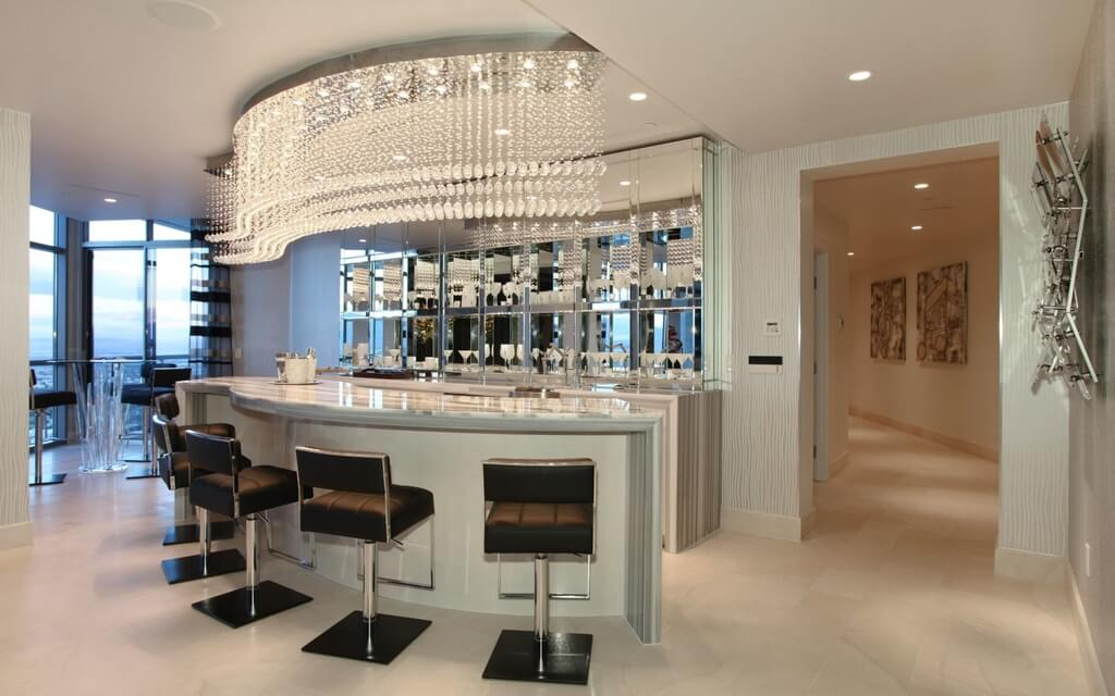Large bar featuring a stunning bar counter paired by black stylish bar stools lighted by a glamorous set of ceiling lighting.