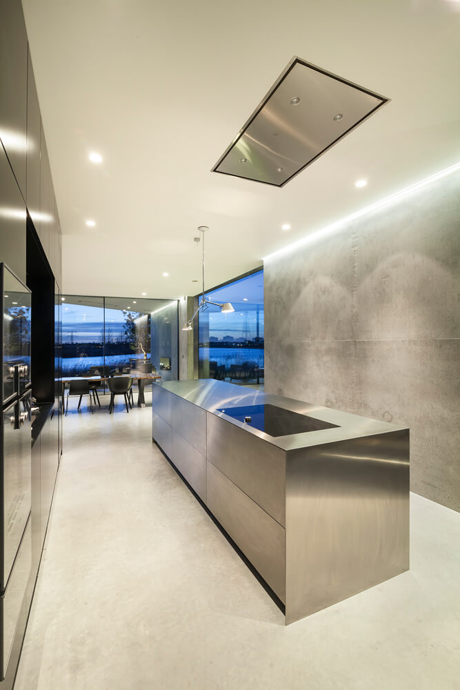 A thoroughly modern stainless steel and concrete kitchen with sleek, clean lines and absolutely no flourishes anywhere in the design. This design merges modern design with industrial.