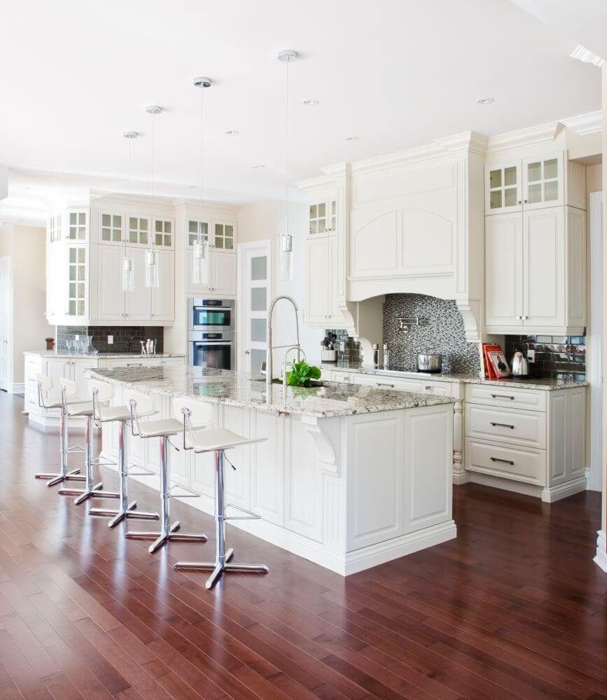 A rich red hardwood floor contrasts beautifully with the white cabinetry and marble countertops of this kitchen, which also features an eat-in bar, glass-faced cabinetry, and a glass mosaic tile backsplash.