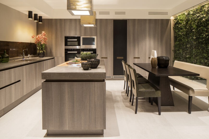 A lovely kitchen with a wall of light gray minimalist cabinets to one side, and a glass wall to the right. Behind the glass wall is a wall of hedges, providing privacy and an organic element to this lovely modern kitchen.