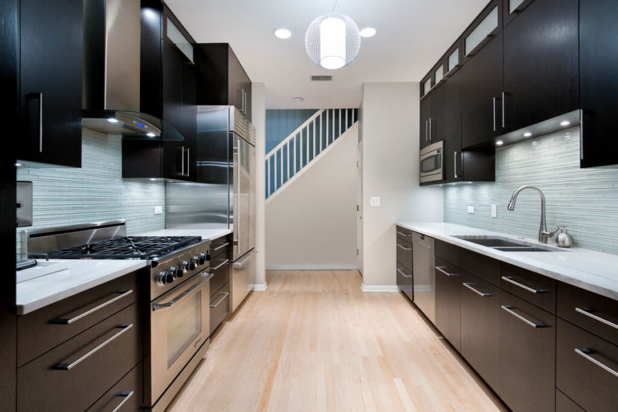 A sleek modern kitchen featuring a glass tile backsplash in light blue-gray. Stainless steel fixtures and a light floor contrast with the rich dark wood cabinetry. Recessed lights surround the single pendant light that is flush with the ceiling.