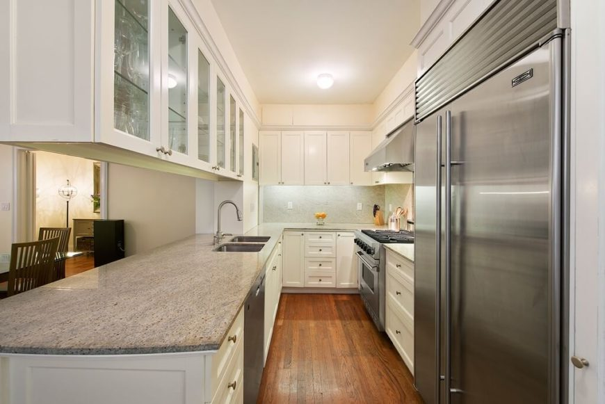 A narrow galley kitchen with a pass-through countertop to the formal dining room. Glass-faced wall cabinets above the passthrough ensure that no vital storage is lost while also allowing this kitchen to feel more open.