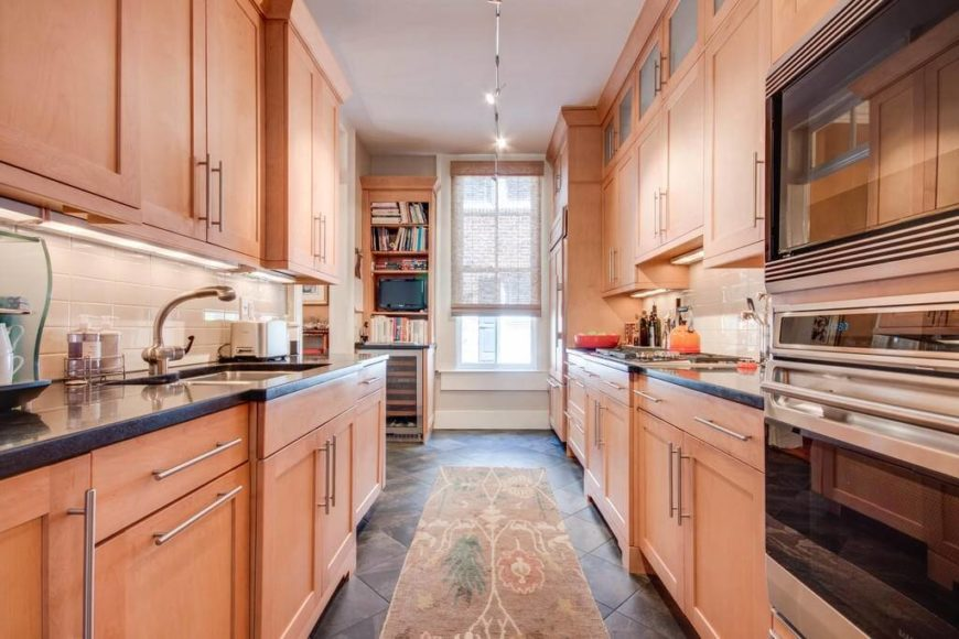 A contemporary light wood galley kitchen with a diamond pattern dark tile floor, high-end appliances, and dark granite countertops. Rail lighting extends down the length of the galley kitchen towards the single window.