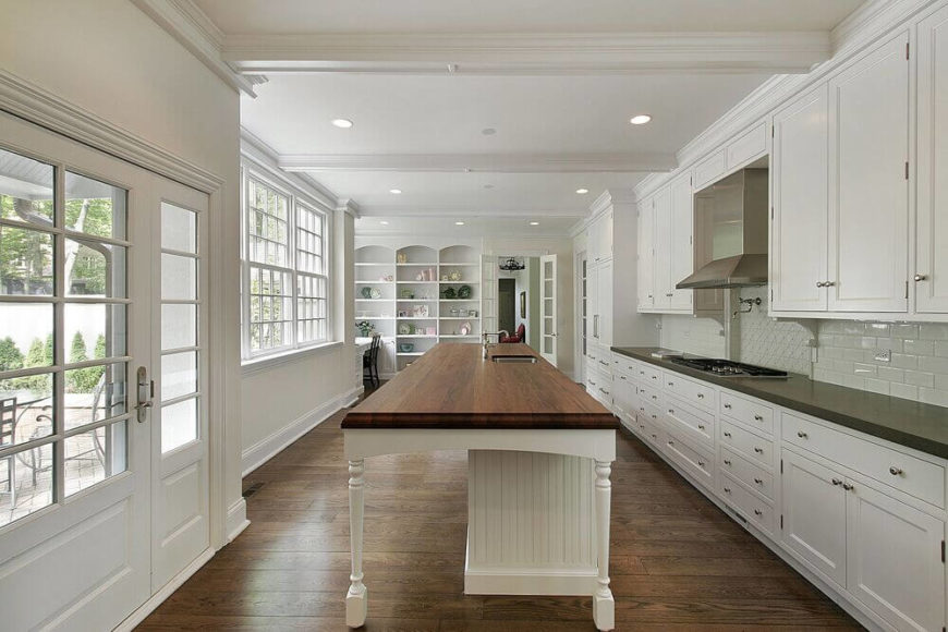 This lengthy white kitchen features a butcher block island with carved legs, expansive windows, and built-in shelving at the end of the space to the left of the French doors. Classic subway tile in the backsplash gives way to a tile mosaic centered behind the stove, as is popular in contemporary design.