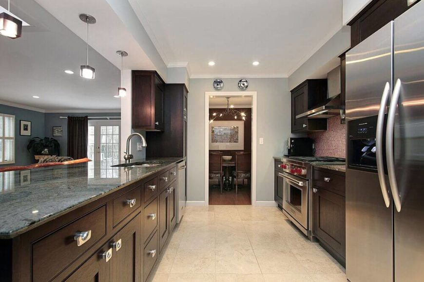 The layout of this contemporary kitchen is wholly rectangular, featuring green-gray granite countertops, dark wood cabinetry, and silver contemporary fixtures that match the stainless steel high-end appliances. The kitchen overlooks a darker blue living room area, and is a great design for entertaining.