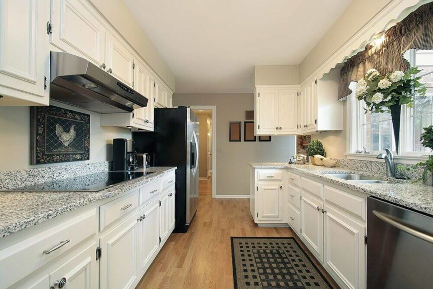 A lovely white kitchen with a few cottage elements to give the kitchen a more quaint atmosphere. The white and gray speckled granite countertops pull color from the dark rug and appliances. A few small houseplants increase the country atmosphere.