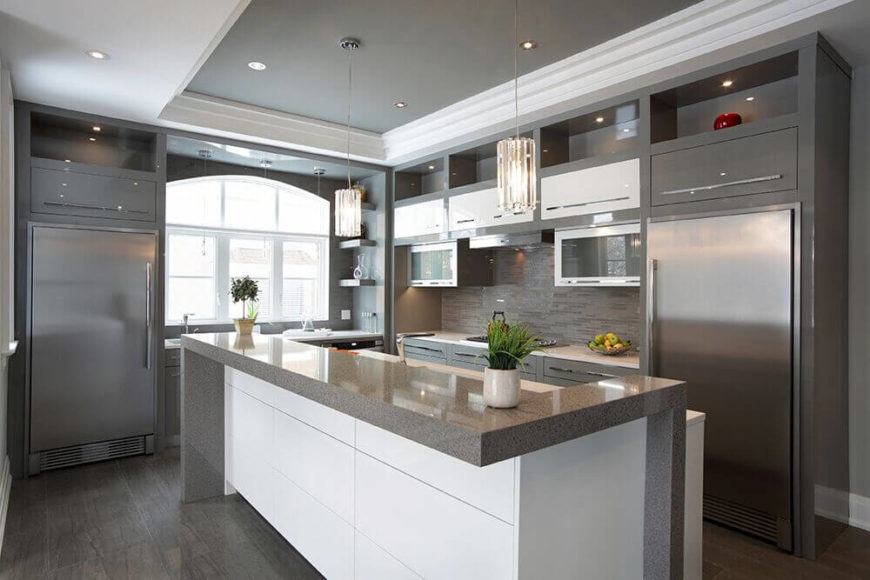 A lovely modern kitchen featuring dark flooring, gray cabinetry and granite countertops, and contrasting white elements. Glitz and glamor are added by two glass pendant lights and a shiny glass mosaic tile backsplash. The room is mostly lit by recessed lighting, and punctuated with pendant lights and natural light from the window.