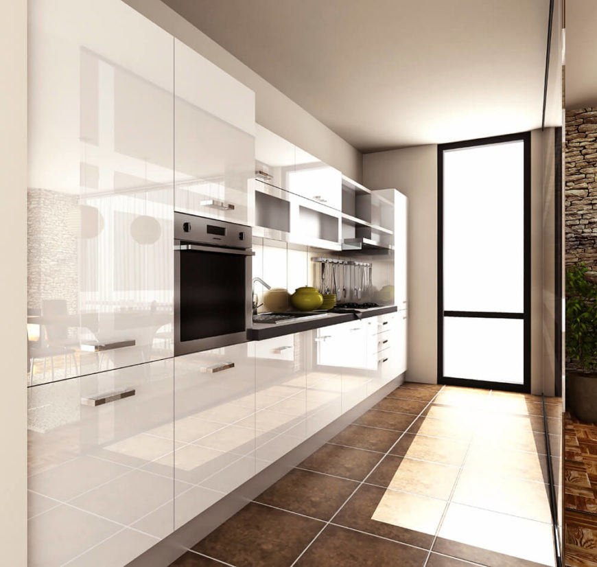 A slim galley kitchen with sleek, glossy white cabinetry and small appliances in stainless steel. A darker brown stone tile floor adds contrast to the minimalist design. A thin barrier separates the kitchen from the more exotic room beyond.