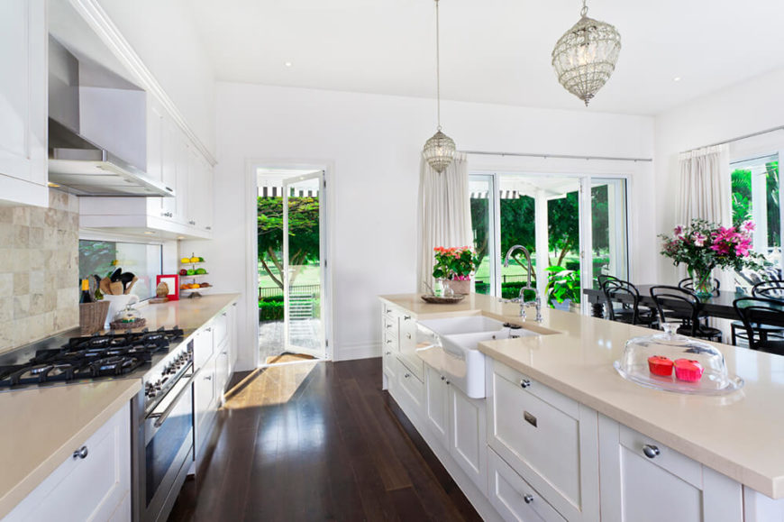 A beautiful dark and light contrasting kitchen with quartz countertops, a dual basin farmhouse sink, and crystal pendant lights having above the lengthy island. On the other side of the island is a large formal dining area surrounded by expansive windows that let in plenty of light.
